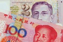 En dollarsedel för två Singapore med den Yuan för hundra kines sedeln arkivfoto