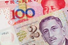 En dollarsedel för två Singapore med den Yuan för hundra kines sedeln fotografering för bildbyråer