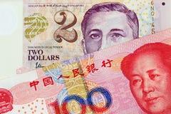 En dollarsedel för två Singapore med den Yuan för hundra kines sedeln arkivbilder