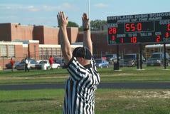 En domare signalerar en landningsögonblick under en högstadiumfotbollgamr royaltyfri bild