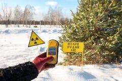 En dosimeterradiometer i handen av en turist, visar ett på hög nivå av utstrålning på platsen av en bränd skog under arkivfoto