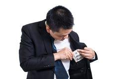 En dräkt för affärsmanklädersvart som sätter pengar i hans isolerade fack på vit bakgrund arkivbilder
