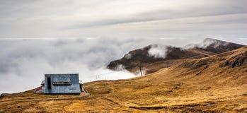 En drömlik bergplats med en chalet och molnräkning på en moun Royaltyfria Foton