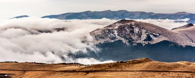 En drömlik bergplats med molnräkningen på en bergkulle Arkivfoto