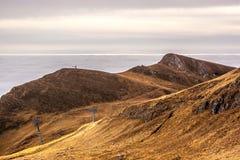 En drömlik bergplats med molnräkningen på en bergkulle PA Arkivbild