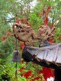 En drake och en klocka på taket av en kinesisk pagod royaltyfria foton
