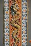 En drake skulpterades på en pelare i borggården av en buddistisk tempel i Thimphu (Bhutan) Arkivfoto