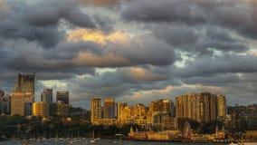 En dramatisk plats av sydney cityscape under en reddidsh och gulaktiga brinnande moln royaltyfria foton