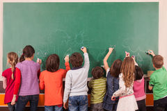 En drGroup of nine pupil drawing on school chalkboard with chalks. Stock Photo