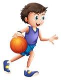 En driftig ung man som spelar basket Arkivfoton