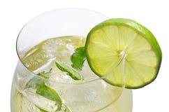 En drink med limefrukt och minten i ett wineexponeringsglas arkivfoton