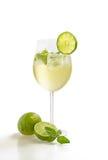 En drink med limefrukt och minten i ett wineexponeringsglas arkivbild