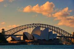 En drmatic plats av rödaktiga och gulaktiga brinnande moln över Sydney husopera och hamnbron royaltyfri bild