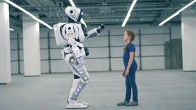 En droid och en flicka som trycker på händer, sidosikt lager videofilmer
