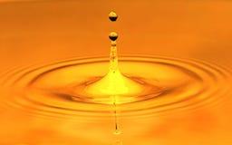 En droppe av vatten faller i ett guld- vatten Makro Royaltyfri Bild