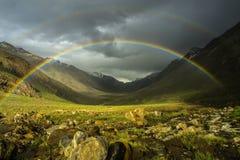 En dubbel ljus regnbåge efter regnet till de höga bergen av dalen: ovanför de gröna fälten är en härlig ljus regnbåge Royaltyfri Fotografi