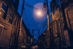 En dunkelt tänd kuslig gränd med den ljusa signalljuset och blå himmel royaltyfri foto