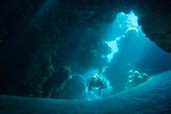 En dykare undersöker sprickorna, sprickorna och hålen i en korallrev på Röda havet Arkivfoton