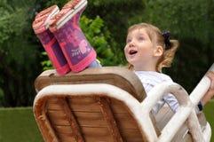 En dynamisk utomhus- stående av en le liten flicka på en gunga arkivbilder