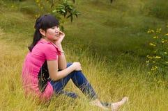 En eftertänksam flicka med ogräs Arkivbild