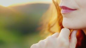En eftertänksam kvinna står på solnedgången, närbild - endast är kanterna och handen synliga i ramen Hon ler lager videofilmer