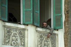 En egyptisk manblick till och med fönstret Arkivfoto