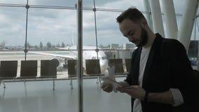 En el aeropuerto en viaje el hombre comprueba un boleto plano en sala de espera almacen de metraje de vídeo