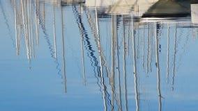 En el amanecer, en el agua refleje los palos de los yates hermosos elegantes blancos Mañana clara del verano en el puerto deporti metrajes