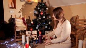 En el ambiente festivo del ` s del Año Nuevo cerca del árbol de navidad, una muchacha sopla hacia fuera una vela púrpura metrajes