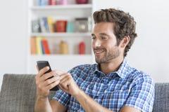 En el apartamento moderno blanco un mensaje que manda un SMS del mediados de hombre adulto en el teléfono móvil Foto de archivo