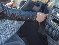En el asiento del ` s del conductor del coche, la muchacha enciende el motor Fotografía de archivo libre de regalías