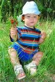 En el bosque una niña que se sienta en la hierba y que lleva a cabo el bke Fotos de archivo