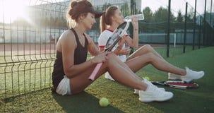 En el campo de tenis en las muchachas del tiempo dos de la tarde que se relajan después del juego que bebe una batalla del agua almacen de metraje de vídeo