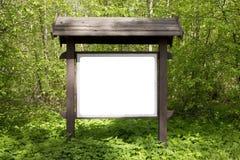 En el claro del bosque de la primavera hay una cartelera de madera con los inf Fotos de archivo