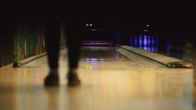 En el club del juego para rodar, el jugador lanza una bola de bolos que golpee abajo bolos Movimiento liso del foco almacen de metraje de vídeo