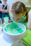 En el dentista la muchacha paciente dental escupe el agua después del tratamiento Foto de archivo libre de regalías