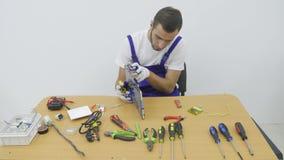 En el electricista del taller que usa los cortaalambres para cortar un pedazo de alambre Los dos hombres espaciosos y trabajo bri almacen de metraje de vídeo