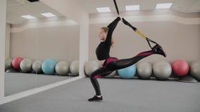 En el entrenamiento del afro una mujer hace ejercicios en las correas suspendidas de TRX en gimnasio Persona femenina fuerte con  metrajes