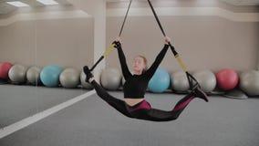 En el entrenamiento del afro una mujer hace ejercicios en las correas suspendidas de TRX en gimnasio Persona femenina fuerte con  almacen de metraje de vídeo