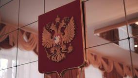 En el espejo la pared en una institución pública cuelga el escudo de armas de la ciudad Primer agradable almacen de video