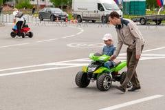 En el festival, los niños montan en los coches grandes del juguete fotos de archivo libres de regalías