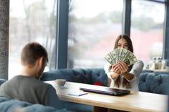 En el foco selectivo de la mujer hermosa que muestra el dinero Reunión del restaurante Imagen de archivo