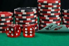 En el fondo de pilas de microprocesadores a jugar en el casino, dos tarjetas dobladas para ver la denominación en la tabla verde, foto de archivo libre de regalías