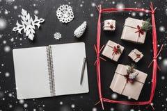 En el fondo negro, muchos regalos y artículos hechos a mano, un folleto donde usted puede copiar un mensaje del saludo Foto de archivo libre de regalías