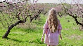 En el jardín de árboles florecientes va la muchacha rubia en vestido rosado almacen de video