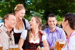 En el jardín de la cerveza - amigos en una tabla con la cerveza Fotografía de archivo libre de regalías