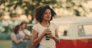 En el ladie hermoso africano de la comida campestre que juega delante de la sonrisa de la cámara, celebrando una botella de cerve almacen de video