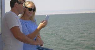 En el mar en la ciudad de Perea, Grecia en un par joven de la nave que hace el selfie en un teléfono móvil