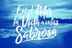 En el mar la vida es mas sabrosa - At sea life is more tasty spanish text, Traditional Latin phrase. Over a blurred beach background Royalty Free Stock Photography