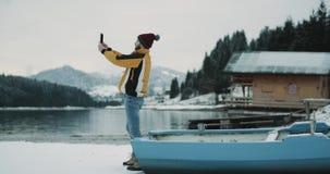 En el medio de la naturaleza con un lago grande y una montaña nevosa y un hombre joven del bosque con la chaqueta anaranjada que  almacen de metraje de vídeo